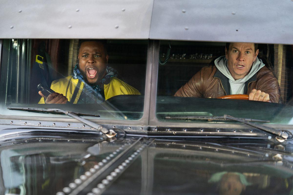 Wahlberg conduce un camión mientras Duke, en el asiento del pasajero, grita.