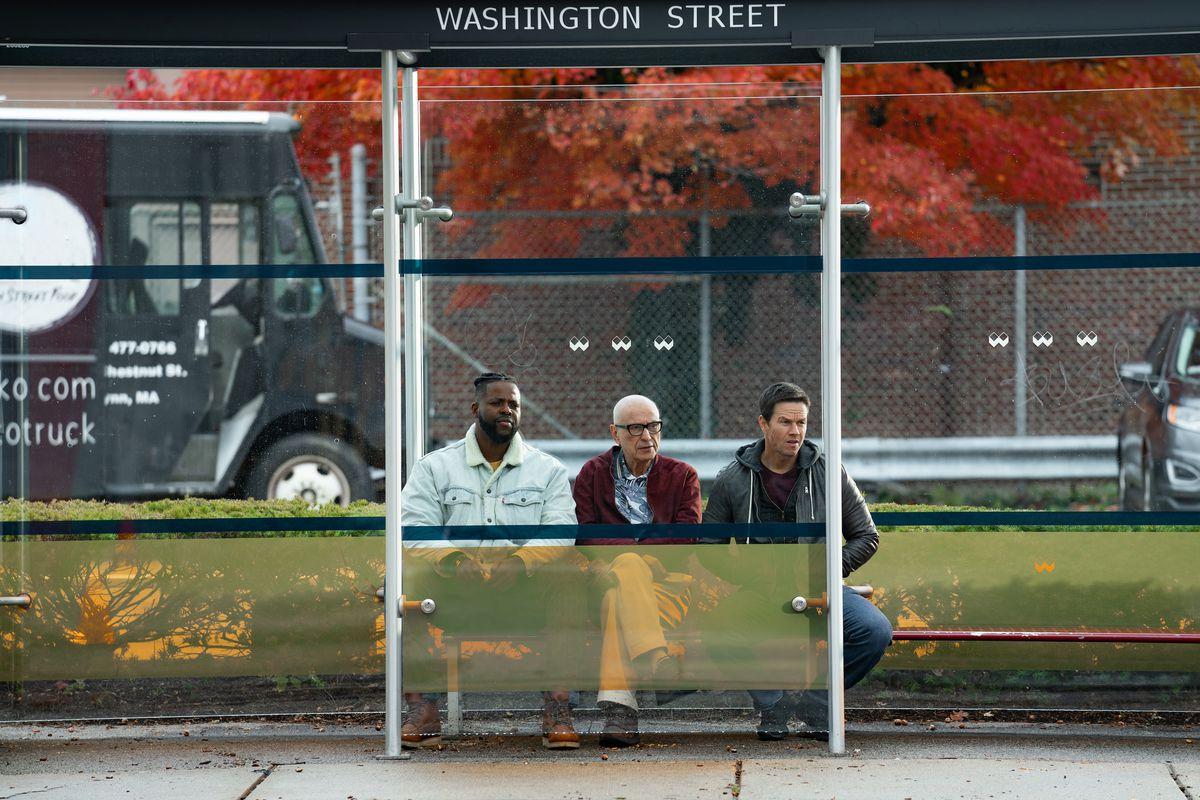 Los tres hombres sentados en una parada de autobús.