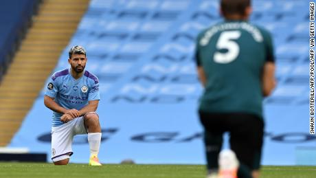 El delantero del Manchester City Sergio Agüero (izq.) Y el defensor de Burnley James Tarkowski se arrodillan, apoyando el movimiento Black Lives Matter.