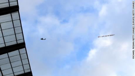 Un avión con una inscripción de pancarta vuela sobre el estadio Etihad