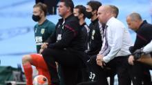 El gerente de Burnley, Sean Dyche (derecha) se arrodilla, apoyando el movimiento Black Lives Matter.