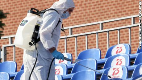 Un trabajador sanitario con ropa protectora rocía un desinfectante en los asientos de la Plaza Roja frente al desfile.