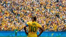La jugadora brasileña Marta está parada frente a una multitud brasileña.