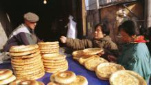 Uighur vende pan plano tradicional a mujeres que compran en la calle Xinjiang en Beijing en 1999.
